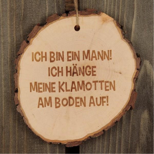 """Die Baumscheibe besteht aus echtem Holz und ist mit dem Spruch """"Ich bin ein Mann! Ich hänge meine Klamotten am Boden auf!"""" graviert."""
