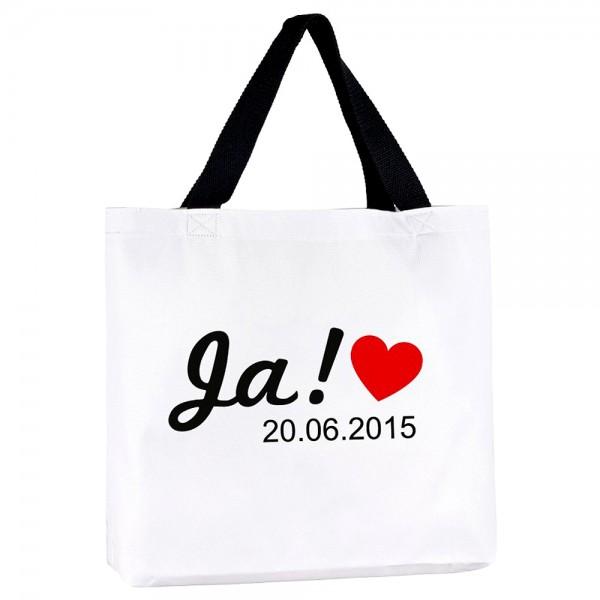 """Die weiße Strandtasche hat einen schwarzen Henkel und ist mit dem Wort """"Ja!"""", dem Hochzeitsdatum und einem roten Herz bedruckt!"""